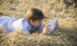 child-in-hay-with-tablet